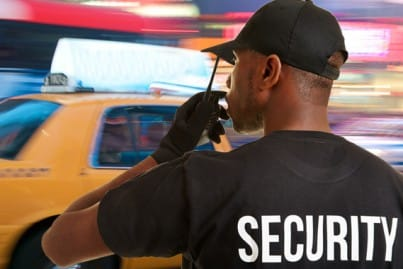 A security guard speaking into a radio and taxi going past to convey the public safety sector