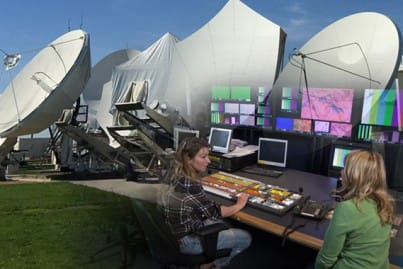 Satellite dishes at a teleport and girls working in a control room