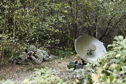 Camoflaged Soldier hidden amongst woodland with a fly away system - portable Satcom dish in army green