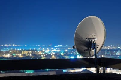 Satellite dish antenna on top of a building in an urban area at night